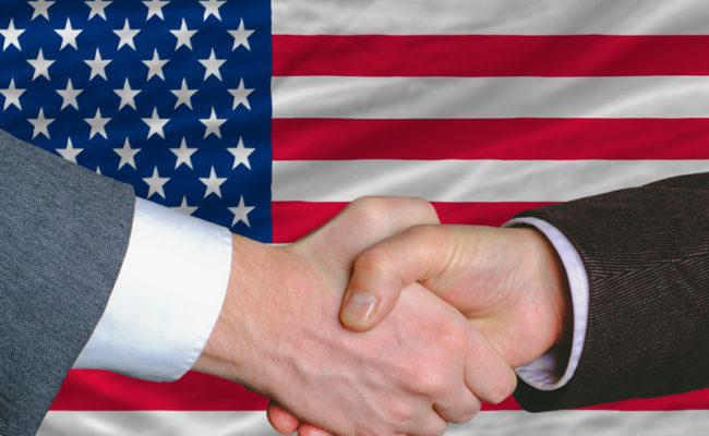 businessmen handshake after good deal in front of america flag